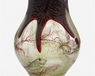 """74 A Daum """"Algues Et Poissons"""" Intercalaire Glass Vase Circa 1898; Nancy, France Etched signature to underside: Daum Nancy [Croix de Lorraine] Designed by Henri Berge, the rotund intercalaire vase with layers of blue and green glass cased in acid-etched burgundy glass depicting a painted polychrome enamel seascape of algae, a hermit crab, and fish motifs 7.25"""" H x 5.25"""" Dia. Estimate: $1,000 - $1,500"""