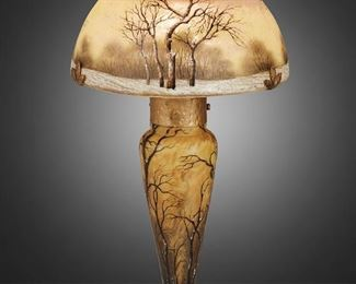 """73 A Daum Cameo Glass And Enameled """"Paysage D'Hiver"""" Boudoir Lamp First-quarter 20th Century; Nancy, France Signed: Daum Nancy [Croix de Lorraine] The acid-etched cameo glass boudoir lamp with enameled winter woodland scene over pink and yellow frost with domical shade on an illuminated and tapered base, electrified Overall: 13.5"""" H x 7.25"""" Dia. Estimate: $7,000 - $9,000"""