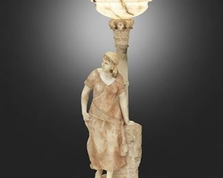 """85 A Greco-Roman-Style Carved Soft Stone Floor Lamp First-half 20th Century Incised: Made in Italy The Greco-Roman-style carved soft stone floor lamp depicting a contrapposto standing woman in front of a figural fountain and Corinthian column surmounted by an illuminated globe with gadrooning and Greek key meander, electrified Overall: 49"""" H x 14.5"""" W x 13.5"""" D Estimate: $2,000 - $3,000"""