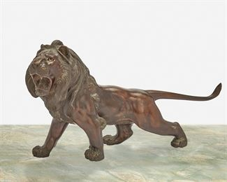 """102 A Japanese Okimono Bronze Lion Meiji period: 1868-1912 Chop mark to base: Takao The bronze okimono in the form of a prowling lion with mouth agape and inset glass eyes 6"""" H x 11"""" W x 2.75"""" D Estimate: $800 - $1,200"""