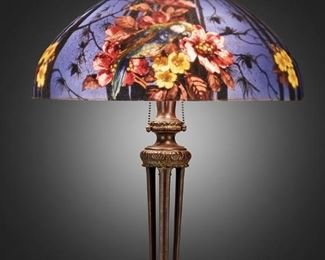 """104 A Handel Reverse-Painted Glass """"Parakeet"""" Table Lamp First-quarter 20th Century; Meriden, Connecticut Shade signed: Handel / Pat'd. No. 979664 / Handel / 7127; Base signed: Handel [cloth label] The domical chipped ice finished glass shade with reverse-painted green and orange parakeets, pink and yellow flowers, and pine trees against a dark blue ground on a three-light bronzed metal tripod base with scrolled anthemion supports and foliate motifs set on a white and grey marble foot, electrified Overall: 24"""" H x 18"""" Dia. Estimate: $3,000 - $5,000"""