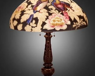 """103 A Handel Reverse-Painted Glass """"Parrot"""" Table Lamp Circa 1923; Meriden, Connecticut Shade signed: Handel / Pat'd. No. 979664 / Handel / 7023; Base signed: Handel The domical, chipped ice finished glass shade with reverse-painted blue and orange parrots and a butterfly among pink and white peonies against a dark charcoal ground on a three-light patinated metal base with knopped column, gadrooning, daisy motifs, and circular foot, electrified Overall: 24.5"""" H x 18"""" Dia. Estimate: $4,000 - $6,000"""
