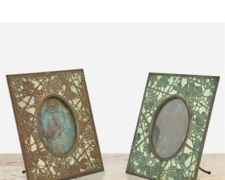 """134 Two """"Grape Vine"""" Bronze Picture Frames First-quarter 20th Century; New York, NY One signed: Tiffany Studios / New York / 946; One unsigned Each rectangular patinated bronze """"Grape Vine"""" frame with green mottled glass and bronze overlay enclosing an oval opening, comprising one with beaded border and one with verdigris patination, 2 pieces Larger: 10"""" H x 8"""" W x 4.5"""" D; Opening: 5.5"""" H x 4"""" W Estimate: $1,500 - $2,000"""