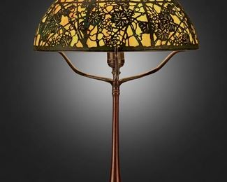 """133 A Tiffany Studios """"Grape Vine"""" Filigree Table Lamp Circa 1902-1919; New York, NY Shade signed: Tiffany Studios / New York; Base signed: Tiffany Studios / New York / 436 The shade with verdigris patinated bronze grape vine motif overlay set against polychrome slag glass panels on a single-light patinated bronze base with ring holder, square foot, and plain column, electrified Overall: 21.5"""" H x 14"""" Dia. Estimate: $5,000 - $7,000"""
