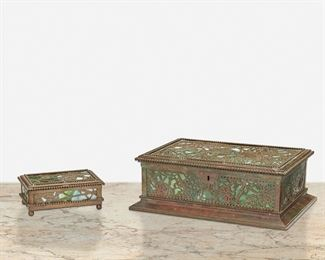 """136 Two Tiffany Studios """"Grape Vine"""" Desk Accessories Circa 1902-1919; New York, NY Each signed: Tiffany Studios / New York; One further marked: 832 Each mottled green glass with patinated bronze """"Grape Vine"""" motif overlay and beaded border, comprising one humidor cigar box with cedar-lined lid and lockplate and one utility box raised on ball feet, 2 pieces Larger: 3"""" H x 9.5"""" W x 6.5"""" D; Smaller: 1.5"""" H x 4.375"""" W x 3"""" D Estimate: $1,200 - $1,800"""