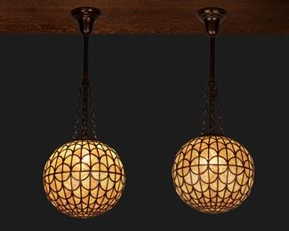 """137 A Pair Of Spherical Leaded Glass Pendant Chandeliers Circa 1900-1910 Each caramel-colored pendant chandelier of painted lead came construction with fish scale pattern fitted with a single light socket and patinated metal stem, canopy, and suspended chain link harness, 2 pieces Each: 31"""" H x 10.5"""" Dia. Estimate: $3,000 - $5,000"""