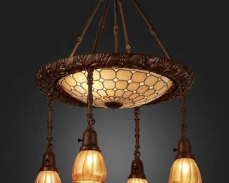 """138 A Leaded Glass And Patinated Metal Chandelier First-quarter 20th Century Three shades signed: Quezal; Fixture signed: Horn and Brannen Mfg. Co. / Philadelphia The two-light patinated metal chandelier with a caramel-colored geometric leaded glass shade enclosed in a wreath-style metal border issuing four drop pendants with gold iridescent Quezal floriform glass shades and reeded hanging shafts, electrified 32"""" H x 21"""" Dia. Estimate: $2,000 - $3,000"""