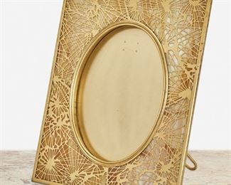 """140 A Tiffany Studios Gilt-Bronze Pine Needle Frame Circa 1902-1919; New York, NY Signed: Tiffany Studios / New York / 919 The rectangular gilt-bronze frame with white and amber mottled glass, pine needle motif gilt-bronze overlay, and beaded border enclosing an oval opening Overall: 11.75"""" H x 9.5"""" W x 6.5"""" D; Opening: 8"""" H x 6"""" W Estimate: $1,500 - $2,000"""