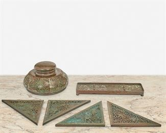 """143 A Group Of Tiffany Studios Pine Needle Desk Set Items Circa 1902-1919; New York, NY Each signed: Tiffany Studios / New York; Further marked: 1004 / 997 / 847 Each patinated bronze with pine needle motif, comprising an inkwell with green glass and bronze overlay, a pen tray with green glass and bronze overlay, and four bronze blotter corners, 6 pieces Largest: 4"""" H x 6.5"""" Dia.; Smallest: .25"""" H x 8"""" W x 4"""" D Estimate: $500 - $700"""