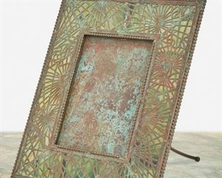 """142 A Tiffany Studios Bronze Pine Needle Frame Circa 1902-1919; New York, NY Signed: Tiffany Studios / New York / 947 The rectangular verdigris patinated bronze frame with green glass, pine needle motif bronze overlay, and beaded border enclosing a rectangular opening Overall: 9.5"""" H x 8"""" W x 6"""" D; Opening: 5.375"""" H x 3.875"""" W Estimate: $1,000 - $1,500"""