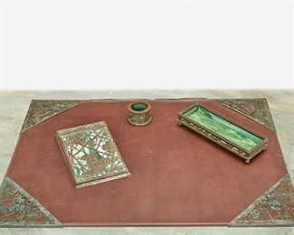 """152 A Tiffany Studios """"Grape And Vine"""" Desk Set Circa 1902-1919; New York, NY Each signed: Tiffany Studios / New York; Further marked: 903 / 981 / 997 Each patinated bronze with green mottled glass and """"Grape Vine"""" motif overlay with areas of verdigris patination, comprising a memoranda pad with wood back, a pen tray, a pen wiper, and four blotter corners, 7 pieces Largest: 7.75"""" H x 4.75"""" W x .75"""" D; Smallest: 1.5"""" H x 1.25"""" Dia. Estimate: $800 - $1,200"""