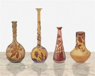 """157 Four Gallé Cameo Glass Bud Vases Late 19th/early 20th Century; Nancy, France Three signed: Galle; One signed: Galle [starred] Each acid-etched cameo glass, comprising one tall-necked vase cut from amber to chartreuse frost with floral motif and flared rim, one tall-necked """"Hawthorn"""" vase cut from amber to white frost, one flared """"Poppy"""" vase cut from amber to pink frost, and one squat """"Fuchsia"""" vase cut from purple to light yellow frost, 4 pieces Largest: 8.5"""" H x 2.75"""" W x 1.5"""" D; Smallest: 4.5"""" H x 3"""" Dia. Estimate: $800 - $1,200"""