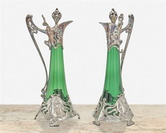 """170 A Pair Of WMF Jungendstil Decanters Circa 1910; Germany First marked: WMFR I/0 OX / C; Second marked: WMFR I/0 AS / I Each flared decanter with emerald green glass inserts and polished pewter mounts with floral motifs and portrait heads, raised on four feet, 2 pieces Each: 16"""" H x 7"""" W x 6.75"""" D Estimate: $1,000 - $1,500"""