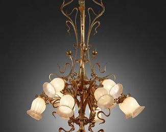 """175 An Art Nouveau Gilt-Bronze Chandelier With Quezal Art Glass Shades First-quarter 20th Century Each shade signed: Quezal The twelve-light gilt-bronze chandelier with central knopped column, foliate canopy, pointed finial, elaborate flowing ribbons, and floral motifs issuing twelve arms terminating in white iridescent Quezal floriform glass shades, electrified 50"""" H x 31"""" Dia. Estimate: $3,000 - $5,000"""