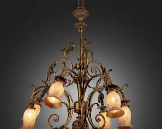 """188 A Rococo-Style Gilt-Bronze Chandelier With Quezal Art Glass Shades First-quarter 20th Century Each shade signed: Quezal The six-light gilt-bronze chandelier with central knopped column, gadrooned canopy, openwork fonts, pointed finial, and scrolling foliage issuing six arms terminating in white and gold Quezal spun glass shades with green leaf motif, electrified 39"""" H x 36"""" Dia. Estimate: $1,000 - $1,500"""
