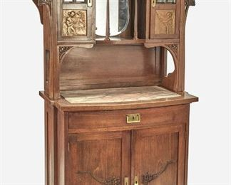 """190 An Art Nouveau Walnut Curio Cabinet Late 19th/early 20th Century The walnut curio cabinet with glazed doors featuring beveled leaded glass and opposed figural repousse gilt-copper inset panels, each concealing a fitted interior with single adjustable shelf, flanking an open tiered center gallery with beveled glass backing, foliate shelf supports, and floral gallery rails over a bow-front console with pink and white inset marble top over one central drawer, two doors with carved floral motif, and fitted interior with one shelf compartment 76"""" H x 41"""" W x 21"""" D Estimate: $1,000 - $1,500"""