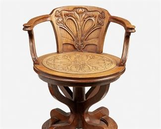 """191 An Art Nouveau-Style Swivel Arm Chair First-quarter 20th Century or later Leather signed: P. Mykytka / 12.19.89 The oak swivel arm chair with figural carved back splat and inset tooled leather seat with floral motif supported by four curved legs 28"""" H x 24.5"""" W x 23"""" D Estimate: $600 - $800"""