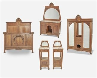 """192 An Art Nouveau Walnut Marquetry Bedroom Set Late 19th/early 20th Century The walnut bedroom set with high relief carved floral details and marquetry portrait roundels with mother-of-pearl inlay, comprising a headboard (66.25"""" H x 57.5"""" W x 4"""" D) and footboard (39.5"""" H x 57"""" W x 1.75"""" D), a two-door mirrored armoire with two open central compartments and four drawers (90.5"""" H x 67"""" W x 23"""" D), a vanity with pink marble top over two drawers and two cupboards with open central compartment (76"""" H x 47.25"""" W x 19.75"""" D), and two side tables each with a mirror and pink marble top over a single drawer and undertray (Each: 43.5"""" H x 15.75"""" W x 15.75"""" D), 6 pieces Estimate: $2,000 - $3,000"""