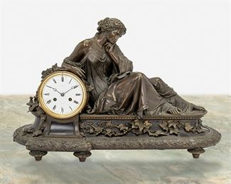 """193 A Tiffany & Co. Bronze Mantel Clock Fourth-quarter 19th Century Dial signed: Tiffany & Co.; Movement marked: 252 20-5 The clock with white metal dial, black Roman numeral hour markers and minute track, Breguet hands, two train movement, and gilt beaded bezel set in a patinated bronze case with inset black stone surmounted by a reclining Greco-Roman woman and tendrils of ivy 19"""" H x 28"""" W x 9"""" D; Dial: 5"""" Dia. Estimate: $2,500 - $3,500"""