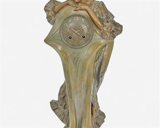 """194 An Art Nouveau Patinated Metal Figural Clock Signed: F. Flora [possibly Francisco Flora] Serial number: 820 The patinated metal clock with low relief gilt Arabic numeral hour markers and two train movement set in a tapered base with a standing female figure 20"""" H x 9"""" W x 7.5"""" D; Dial: 3.5"""" Dia. Estimate: $400 - $600"""
