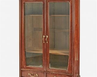 """203 An Art Nouveau Walnut Double-Door Bookcase Late 19th/early 20th Century The walnut bookcase with arched bonnet with high relief carved lily pads atop two glazed doors with gilt-metal handles and an adjustable shelved interior over two drawers with gilt-metal handles raised on four bracket feet 96"""" H x 52"""" W x 20"""" D Estimate: $2,000 - $3,000"""
