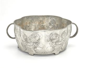 """206 An Archibald Knox For Liberty & Co. Tudric Pewter Bowl First-quarter 20th Century; England Marked: Tudric / 0755 / 7 / Made in England Designed by Archibald Knox for Liberty & Co. of London, the scallop-form footed pewter bowl with opposed handles and low relief Celtic Revival-style scrolling foliage raised on six feet 4.25"""" H x 11.25"""" W x 8.75"""" D Estimate: $400 - $600"""