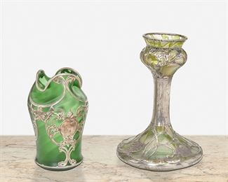 """210 Two Art Nouveau Loetz-Style Sterling Silver Overlay Glass Vases Late 19th/early 20th Century One marked: 999/1000; One marked for La Pierre; Further marked: Sterling Comprising an iridescent green vase with leaf motif overlay and an emerald green vase with satin finish with foliate and flower motif overlay, 2 pieces Larger: 9"""" H x 6"""" Dia.; Smaller: 6.75"""" H x 4"""" Dia. 36.230 gross oz. troy approximately Estimate: $600 - $800"""
