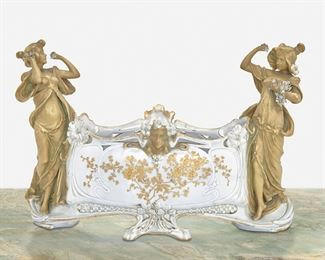 """213 An Austrian Jugendstil Ceramic Centerpiece Late 19th/early 20th Century; Austria Marked: Made in Austria / 4635 / 223 / 5 The ovoid ceramic centerpiece with gilt-highlight floral sprays surmounted by figural masks, flanked by two standing female figures, and raised on two central feet 12.5"""" H x 18"""" W x 7.25"""" D Estimate: $600 - $800"""