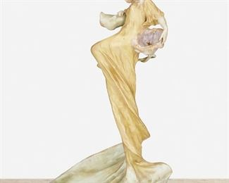 """214 An Amphora """"Dancing Lady With Flowers"""" Vide Poche Late 19th/early 20th Century Marked: Amphora / Riessner, Stellmacher & Kessel [RStK] Turn-Teplitz Bohemia / Made in Austria / 777 / 4 The ceramic vide poche with a low dish base and depicting a dancing woman in a yellow dress with a purple morning glory flower and gilt highlights throughout 16"""" H x 7.75"""" W x 9.5"""" D Estimate: $500 - $700"""