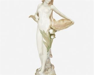 """216 An Austrian Jugendstil Ceramic Standing Nude Late 19th/early 20th Century; Austria Marked: Made in Austria / 4638 / 1 The ceramic standing nude depicting a female figure surrounded by pink and green lily pads atop a rocky base with sea shells 16.5"""" H x 7.5"""" W x 6"""" D Estimate: $500 - $700"""