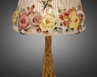 """218 A Pairpoint Reverse-Painted Puffy Glass """"Devonshire"""" Table Lamp 1907-1929; New Bedford, Massachusetts Shade: unsiged; Base signed: Pairpoint Mf'g. Co. [""""P"""" diamond monogram] / 3091 The mold-blown puffy and frosted glass """"Devonshire"""" shade with reverse-painted polychrome roses and hummingbirds against opaque white stripes and torch and wreath motif on a single-light gilt-bronze tree trunk base with circular foot, electrified Overall: 23"""" H x 15.5"""" Dia. Estimate: $2,000 - $3,000"""