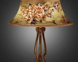"""219 A Pairpoint Reverse-Painted Glass """"Exeter"""" Table Lamp 1907-1929; New Bedford, Massachusetts Shade signed: The Pairpoint Corp.; Base signed: Pairpoint [""""P"""" diamond monogram] / D 3084 <br> <br> <br> <br> <br> <br> <br> <br> <br> <br> <br> <br> The bell-form frosted glass """"Exeter"""" shade with reverse-painted polychrome floral motif against a green ground with yellow borders on a three-light brass tripod base with three scrolled supports raised on a triform foot, electrified Overall: 21"""" H x 17"""" Dia. Estimate: $1,000 - $1,500"""