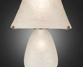 """230 A Daum Art Deco Etched Glass Table Lamp Second-quarter 20th Century; Nancy, France Base and shade signed: Daum Nancy / France [Croix de Lorraine] The acid-etched clear glass table lamp with frosted geometric square and wave-form designs throughout, the domical shade with scalloped border atop a bulbous base with Edgar Brandt hammered metal hardware, electrified Overall: 18"""" H x 13"""" Dia. Estimate: $2,000 - $3,000"""