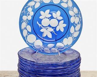 "236 Twelve Pairpoint Cobalt Blue Art Glass Fruit Plates First-quarter 20th Century; New Bedford, Massachusetts Each cobalt blue glass cut to clear with engraved fruit motif, 12 pieces Each: 1"" H x 10.5"" Dia. Estimate: $500 - $700"