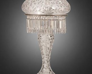 """238 An American Brilliant Cut Glass Table Lamp Late 19th/early 20th Century The two-light Brilliant cut glass lamp with domical shade, hanging crystal skirt, tapered base, and sawtooth scalloped edge foot with leaf and flower motif throughout, electrified Overall: 29"""" H x 14"""" Dia. Estimate: $1,500 - $2,000"""