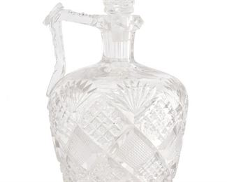 """240 An American Brilliant Cut Glass Whiskey Jug Late 19th/early 20th Century The Brilliant cut glass handled whiskey jug and stopper with fine crosshatching, strawberry diamond cuts, fan motifs, cut ovals, a hobstar base, and handle with facet-cut patterning 9"""" H x 5.25"""" Dia. Estimate: $600 - $800"""