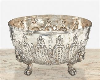 """245 An English Sterling Silver Fruit Bowl Circa 1818-1819 Marked for sterling The sterling silver bowl with reeded rim and repousse foliate motifs raised on three ball and claw feet surmounted by lion masks, monogrammed and engraved with lion rampant 7.5"""" H x 12.25"""" Dia. 78.44 oz. troy approximately Estimate: $1,000 - $1,500"""