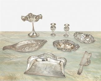 """249 Eight American Art Nouveau Sterling Silver Items Late 19th/early 20th Century Each marked for sterling; Various makers Comprising a raised repousse compote with floral motif and ribbon edge, a pair of Foster & Bailey diminutive vases with figural masks and fish motif, a Shreve & Co. dust tray and crumber with iris motif, a Wallace repousse oval tray with floral motif, and a pair of William B. Kerr & Co. repousse bon-bon dishes with floral motif, 8 pieces Largest: 6.5"""" H x 6.5"""" Dia. 35.275 oz. troy approximately Estimate: $400 - $600"""