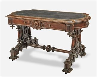 """258 A Victorian Renaissance Revival Library Table Third-quarter 19th Century The mahogany library table with squared corners, rounded sides, and inset black leather writing surface with gold foil acanthus leaf border over a single divided frieze drawer with carved key frame, supported by openwork carved and turned trestle-style legs joined by a turned stretcher raised overall on four block pedestal feet with castors 29"""" H x 51"""" W x 29"""" D Estimate: $1,000 - $1,500"""