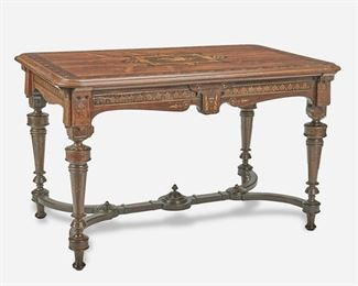 """261 An American Renaissance Revival Marquetry Library Table Second-half 19th Century The Renaissance Revival/Eastlake transitional library table with central millinery motif and floral border marquetry to top over an anthemion motif marquetry apron supported by four turned tapering legs joined by an H-stretcher with incised gilt details throughout 28.5"""" H x 47.75"""" W x 29.5"""" D Estimate: $1,000 - $1,500"""