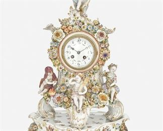 """262 A Capodimonte Mantel Clock With Matching Base First-half 19th Century; Naples, Italy Each marked with blue underglaze crowned """"N""""; Movement serial number: 334 24 The porcelain mantel clock designed with applied flowers, floral sprays, and gilt highlights, comprising a footed clock with two-train movement and white enameled dial with black Arabic numeral hour markers, minute track, and floral festoons encircled by a floral garland and four putti, raised on a three-footed stand, 2 pieces Overall: 22"""" H x 13.75"""" W x 8.5"""" D Estimate: $1,000 - $1,500"""