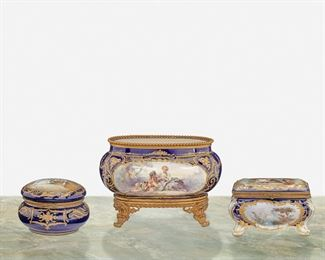 """265 A Group Of French Sèvres-Style Porcelain Items Second-half 19th Century Each variously marked Each with gilt-highlight scrolled foliate motif against cobalt blue ground, comprising a small footed jardiniere with central pastoral figural scene mounted with gilt-bronze beaded rim and four flared feet, a rectangular hinged dresser box with figural and landscape scenes, and a circular hinged dresser box with figural scene to lid, 3 pieces Largest: 6.5"""" H x 9.5"""" W x 6"""" D; Smallest: 4"""" H x 5.75"""" Dia. Estimate: $1,000 - $1,500"""