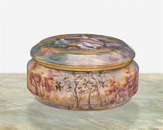 """266 A Limoges Enamel Vanity Box Second-half 19th Century; France Signed: Gamet / France The circular enamel-over-metal vanity box with pastoral figural scene depicting a courting couple to the lid and woodland scene to the base 3"""" H x 6"""" Dia. Estimate: $600 - $800"""