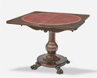 """272 An English Rosewood Flip-Top Game Table Second-quarter 19th Century The game table with pivoting hinged flip-top with inset circular leather panel and concealed compartment over a carved apron supported by a tapered pedestal on a circular platform raised overall on four paw feet Open: 27.75"""" H x 35.75"""" W x 34.875"""" D; Closed: 27.75"""" H x 36"""" W x 17.5"""" D Estimate: $700 - $900"""