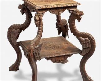"""273 A Continental Carved Wood Side Table Fourth-quarter 19th Century The two-tiered side table with carved floral roundels against a basketweave patterned ground over acanthus leaf motif drops supported by four zoomorphic carved griffin legs with paw feet 27.5"""" H x 23.5"""" W x 22"""" D Estimate: $500 - $700"""