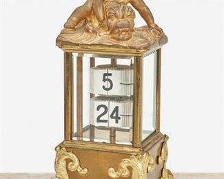 """276 A French Gilt-Bronze Perpetual Desk Calendar First-quarter 20th Century Marked: France; Serial number: 1469 The gilt-bronze perpetual calendar with black Arabic numeral tiles in a glazed case surmounted by a putti riding a dolphin and raised on four dolphin feet 8.5"""" H x 4"""" W x 4"""" D Estimate: $600 - $800"""