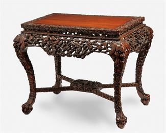 """277 A Chinese Carved Wood Console Table 19th Century The carved wood console table with inlaid top enclosed by a carved border over an elaborate openwork apron with dragon motifs supported by four zoomorphic dragon legs joined by an X-stretcher raised overall on ball-and-claw feet 30"""" H x 39.5"""" W x 25"""" D Estimate: $2,000 - $3,000"""