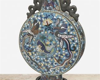 """279 A Large Chinese Cloisonné Moonflask First-quarter 20th Century The enamel cloisonne moonflask with flat circular body, tapered cylindrical neck, and two scrolled handles raised on a flared foot with all-over polychrome dragon, fish, and foo dog motifs against a blue ground set atop an openwork carved wood stand Overall: 17"""" H x 10"""" W x 6"""" D Estimate: $1,000 - $1,500"""