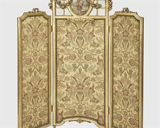 """287 A French Gilded Three-Panel Embroidered Screen Late 19th/early 20th Century Centering a painted panel of a peasant with basket of flowers over a jacquard-lined three-panel screen adorned with carved giltwood swags and flowers 61.5"""" H x 60"""" W x 3.5"""" D Estimate: $800 - $1,200"""