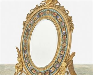 """288 An Alphonse Tahan Cloisonné Enamel And Gilt-Bronze Table Mirror Third-quarter 19th Century; Paris, France Signed: Tahan / Fournisseur de L'Empereur The oval easel-back gilt-bronze frame with floral garlands and putti surrounding a cloisonne enameled border and enclosing an oval glass mirror 10"""" H x 7.25"""" W x 5.5"""" D Estimate: $800 - $1,200"""